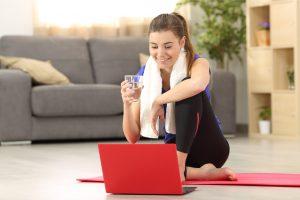 une élève boit un verre d'au après un cours de Pilates en ligne